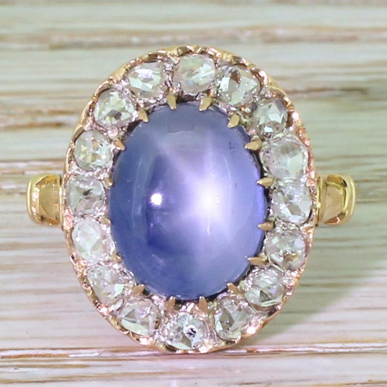 Hypnotically lovely. The large, greyish blue sapphire almost glows from within and displays a lovely, distinct asterism. Sixteen bright white rose cut diamonds surround the centre stone in a beautifully refined pierced gallery. The tri-split