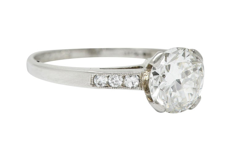 Cathedral basket engagement ring centers a transitional cut diamond  Weighing in approximately 1.10 carats with J color and VS clarity  Set by wide prongs and flanked by milgrain shoulders accented by single cut diamonds  Weighing in total