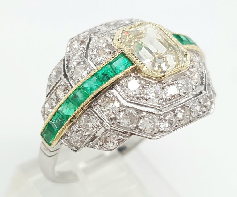 This fine Art Deco ring is a true treasure kept in excellent condition. The ring is an example of pure excellance and its unique design is one of a kind. The center is a stunning 1.24 carat emerald cut diamond and it is bezel set with a delicate