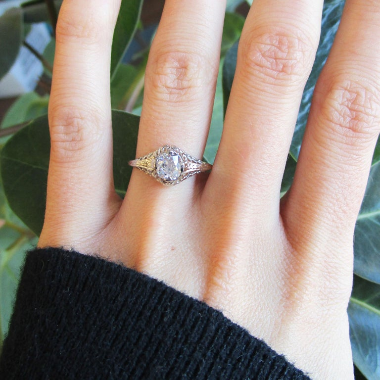 This is a breathtaking Art Deco engagement ring in 14k white gold with gorgeous filigree detailing and a stunning diamond center stone! The filigree detailing encircles the center of the ring and seeps down over the shoulders, filling the top of