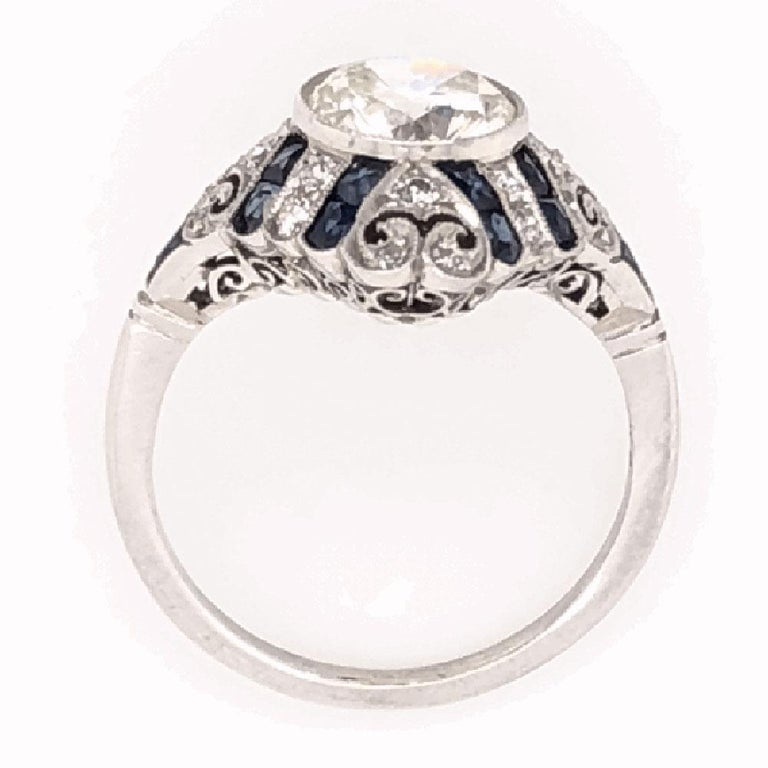Simply Beautiful, Elegant & finely detailed Art Deco style Platinum Ring center set with a securely nestled Antique Round cut Diamond, weighing approx. 1.52 total Carat weight, enhanced with Blue Sapphires approx. 1.21 total Carat weight. Ring size