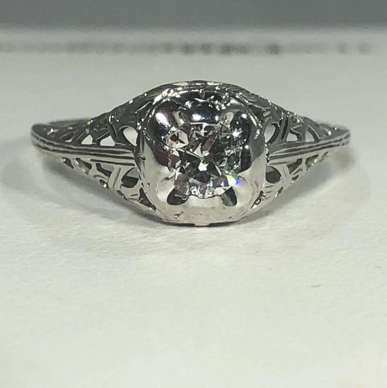 Art Deco 18 karat and old European cut diamond solitaire engagement ring. This is a true antique Art Deco ring, Circa 1925. This piece is created in 18 karat white gold, beautiful cut out filigree design, weighing 1.7 grams, 1.1 DWT. The center