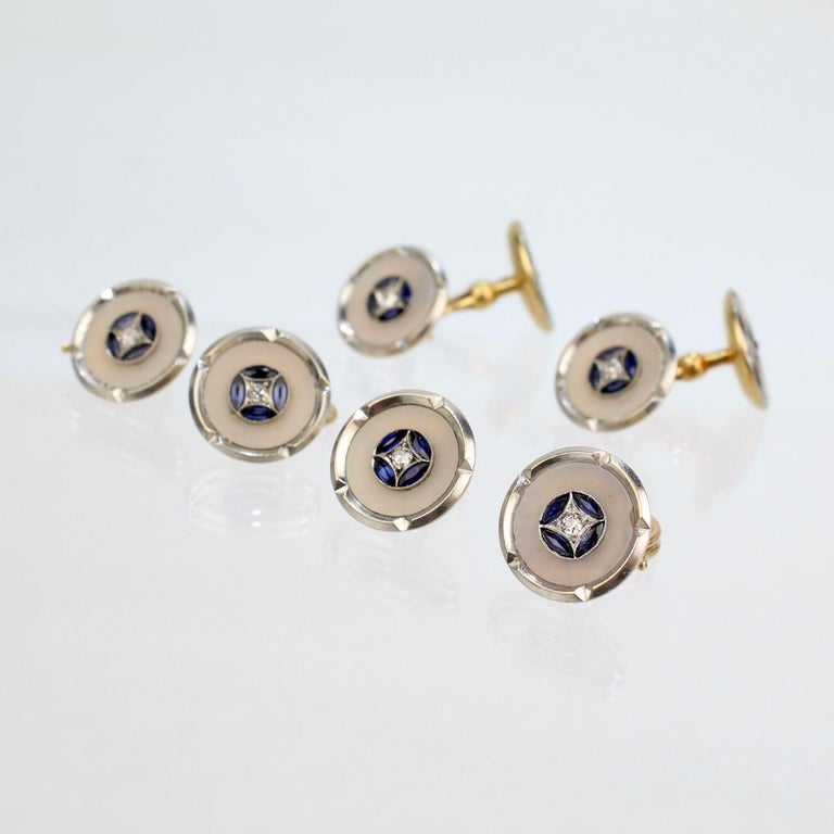 A very fine Art Deco cufflink and button set.  Comprised of 4 shirt buttons and a pair of cufflinks.  In platinum-topped 18k gold and set with diamonds, sapphires, and mother of pearl.  Marked to the reverse: 750 for gold fineness and with a barely