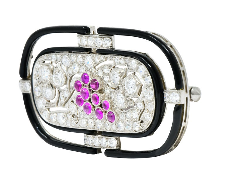 Designed as an oblong platinum brooch featuring round brilliant cut diamonds bead set throughout, weighing approximately 1.80 carats total, E/F color and VS clarity  With 10 bezel set ruby cabochons in a grape cluster motif, deep pinkish hue and