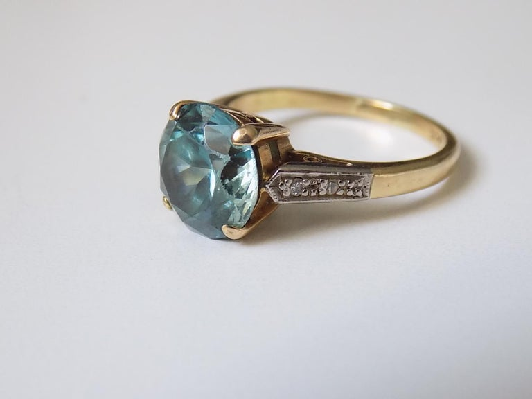 A Stunning Art Deco approx 4 Carat Blue zircon ring in 18 Carat yellow and white gold and on Diamond shoulders. English origin. Size K UK, 5.5 US. Height of the face 9mm. Weight 4.6gr. Marked 18CT for 18 Carat Gold
