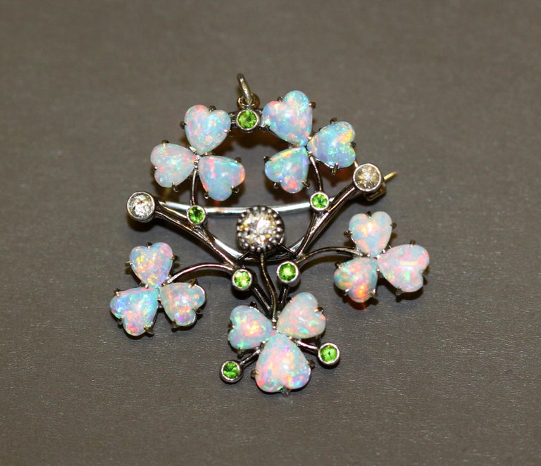 Art deco 18k white gold ladies brooch / pendant with natural heart cut opals in the form of flower petals, along with natural peridots and old cut diamonds.   Made in France   Dimensions -  Size : 3.6 x 3.4 x 0.9 cm  Weight: 7 g   Opal -  Cut :