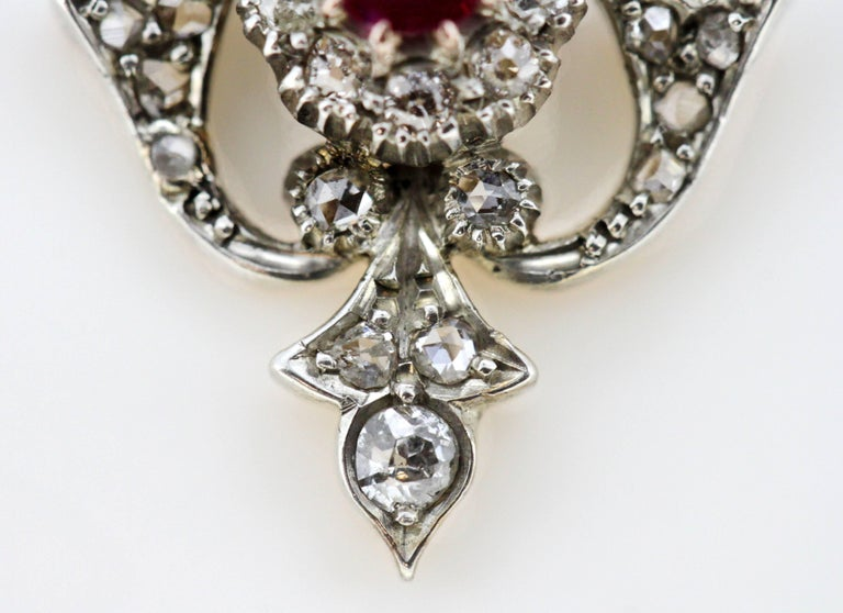 Art Deco 18K White Gold Pendant With Ruby & Diamonds Circa.1920's  Dimensions - Size : 4.3 x 2.35 x 0.6 cm Weight: 3 g  Ruby -  Cut : Oval Size : 0.5 CT Treatment : Natural  Diamond -  Number of Diamonds : 42 Cut : Old Cut Round Carat : 0.56 ct.