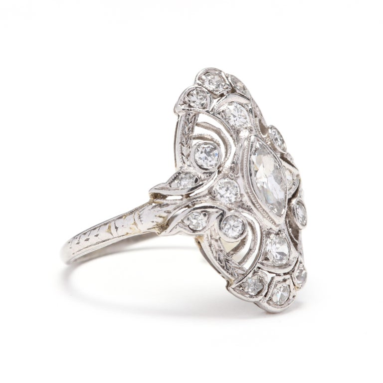 Art Deco 18 karat white gold diamond navette ring. This ring features a marquise center stone with single cut diamond detailing. It is finished with filigree and engraving detail.  Diamonds: approximately .75ctw  2.62 dwts  Size 6.75  * Please note
