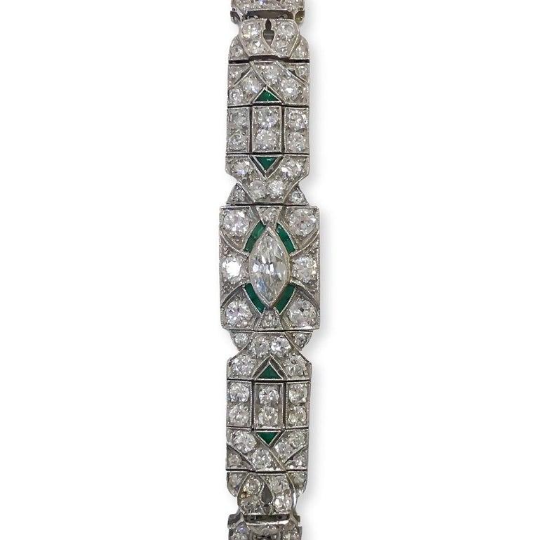 Spectacular authentic Art Deco 1920's bracelet designed in Platinum with milgrain detail. Contains bead set antique round diamonds, one (1) channel set antique marquise cut diamond and twelve (12) natural green emeralds accenting around center