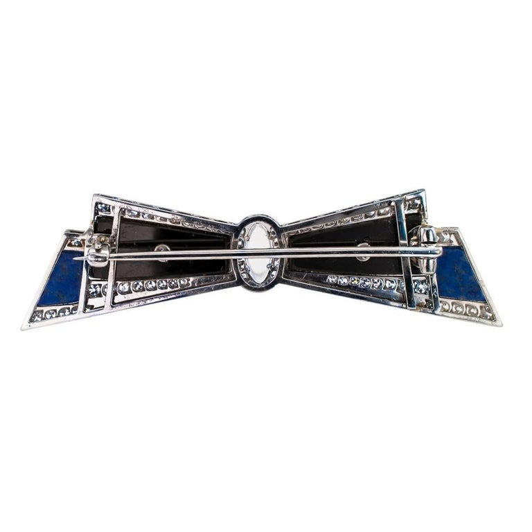 Art Deco 1925 bow brooch diamonds moonstone lapis lazuli onyx and platinum. This most unique Art Deco bow brooch is set with sixty diamonds totaling approximately 1.00 carat, and inlaid with black onyx and lapis lazuli with a navette-shaped