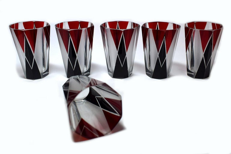 Art Deco 1930s Czech decanter set in clear glass with black and deep red enamel decoration. The decanter comes with six matching glasses, the whole being heavily enamelled with geometric decoration. The lid is made from metal and just slots on top,