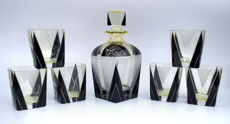Very stylish and appealing Art Deco decanter set which comes with six matching glasses, and decanter, the whole being heavily enameled with geometric decoration. The color is a lemon yellow with black enameling and etched accents and the condition