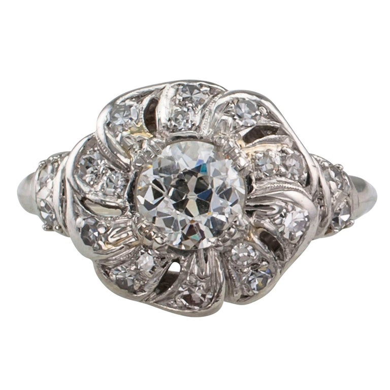 Late Art Deco 1930s diamond and platinum engagement ring. Designed as a flower centering an old European-cut diamond weighing approximately 0.60 carat, approximately I - J color and SI clarity, surrounded by petals to the shoulders set with smaller