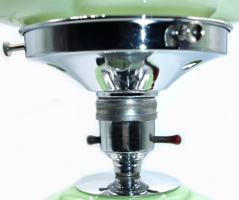Stylish 1930s Art Deco table lamp in a pale pea green glass. Both the body and the shade are matching colored glass, supported on a chrome circular plinth, chrome bulb holder and gallery. The baluster shaped body is segmented and the shade is made