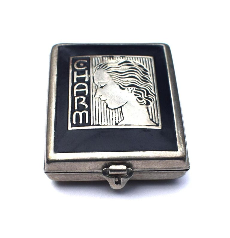 A rare little gem is this delightful 1930's Art Deco ladies powder compact. Classic chrome and black enamel which depicts the profile of a stylized Art Deco lady and the embossed letters 'Charm'. Comes with original rouge and applicator pad inside,