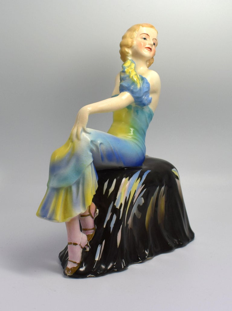 A beautiful, elegant, stylish, Art Deco lady figurine seated on a draped seat. She is in excellent condition with no cracks, chips or restoration. There is some crazing to the glaze, which can be seen on very close inspection. She's been very