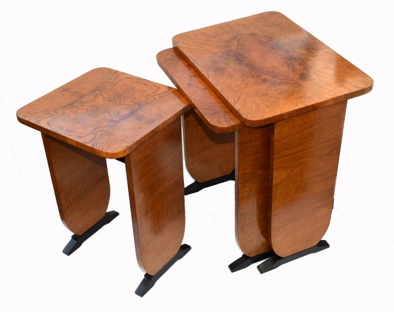 A very stylish and distinctive Art Deco nest of walnut tables dating to the 1930s. One large table with two further tables in tiered sizes that snugly fit underneath each other. Each table is sturdy in it's construct and will work perfectly for