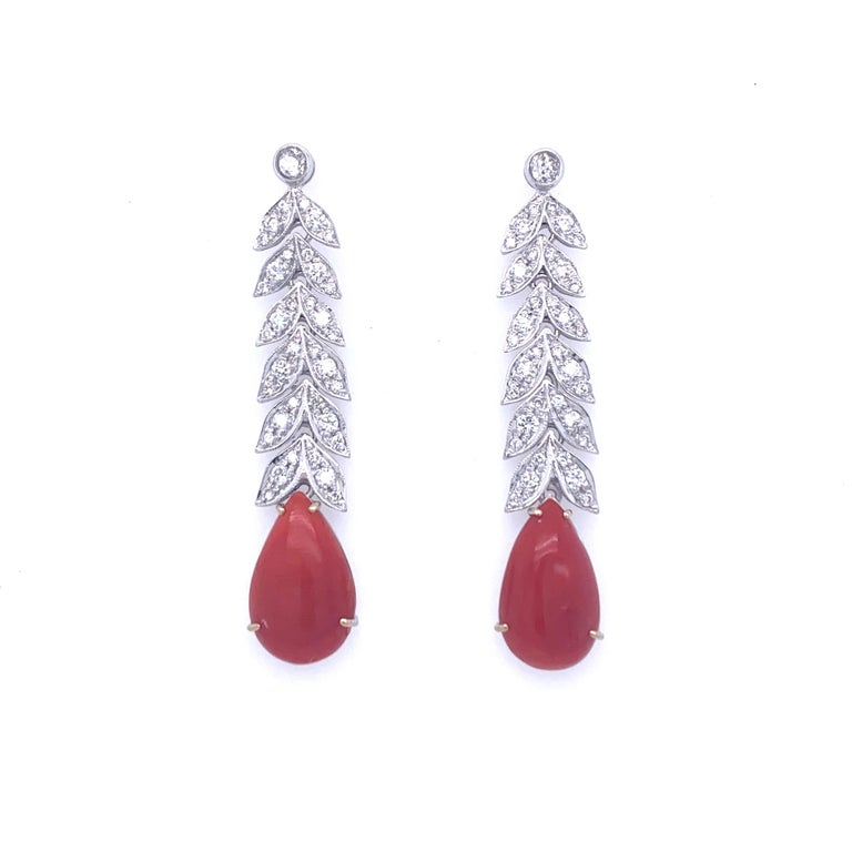 These Beautiful Art Deco 18k white gold earrings feature at the bottom 2 large drop natural Aka Coral, connected by leafs design links set with colorless round Diamonds graded G Color Vvs Clarity and weighing approximately 2.00 carat. Circa