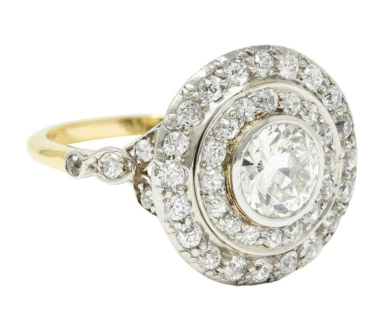 Centering a transitional cut diamond weighing 1.31 carats - I color with SI2 clarity  Bezel set and surrounded by double circular halos of old European cut diamonds  With stylized foliate cathedral shoulders also accented by old European cut