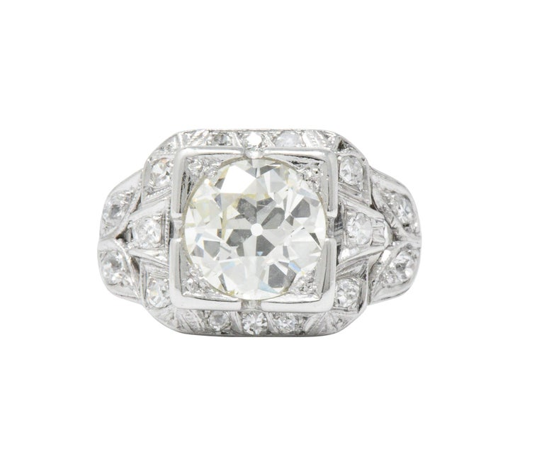 Centering an old European cut diamond weighing 2.34 carats total, N color with VVS2 clarity  Set low in a square form head in a cushion surround flanked by foliate motif shoulders  Accented throughout by single cut diamonds weighing approximately