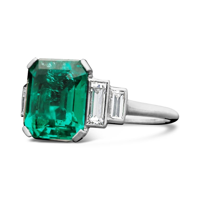 A stunning Art Deco emerald and diamond ring c.1925, centred with a beautiful 3.20ct Colombian emerald-cut emerald in corner-claw setting between shoulders set with stepped baguette cut diamonds, all in a handmade platinum mount.  3.30ct Colombian