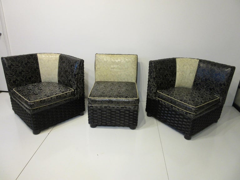 A three-piece love seat or sofa with black and white upholstered cushions with embossed amoeba styled designs. The frame is a painted black wraparound woven wicker with rounded wooden legs having spring supports for the seat cushions. The pieces can
