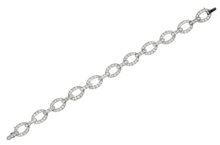 Bracelet is comprised of oval links alternating with bar spacer links  Accented by milgrain and bead set throughout by transitional cut diamonds  Weighing in total approximately 4.25 carats with G to J color and SI clarity  Completed by a concealed
