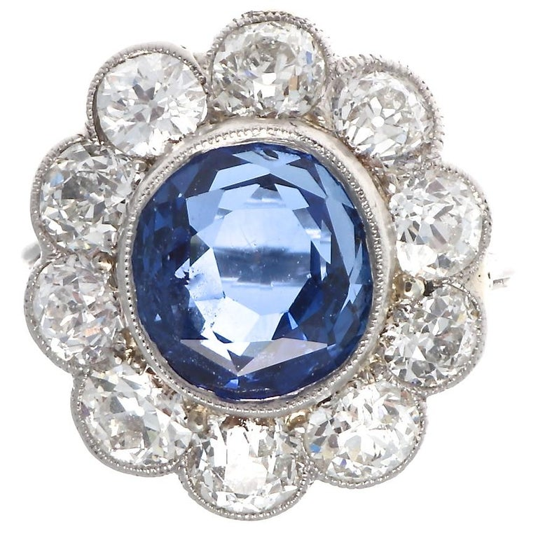 The iconic cluster design that is modeled after a blossoming daisy. Featuring a 4.82 carat GIA certified Burma sapphire that has no indications of heat treatment and displays a deep vivid blue color. Surrounded by pedals of old cut near colorless