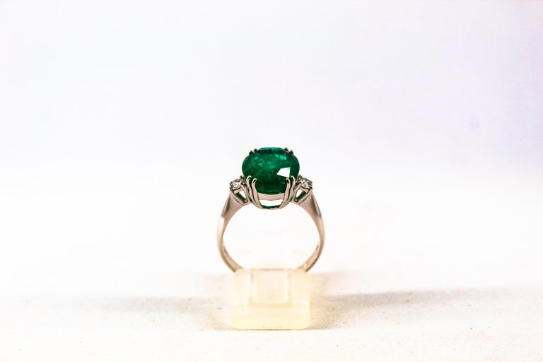 This Ring is made of 18K White Gold. This Ring has 0.20 Carats of White Modern Round Cut Diamonds. Color: H-G Clarity: VVS1 This Ring has a 6.29 Carats Natural Zambia Oval Cut Emerald. This Ring is inspired by Art Deco. Size ITA: 17 USA: 8 We're a