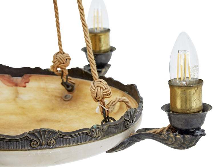 Art Deco alabaster 4-arm ceiling pendant light, circa 1930.  Good quality Art Deco period light. Fitted with 4 cast arms each with a bulb holder and a further bulb holder in the dish. Suspended by 4 ropes up to a central bronzed ceiling