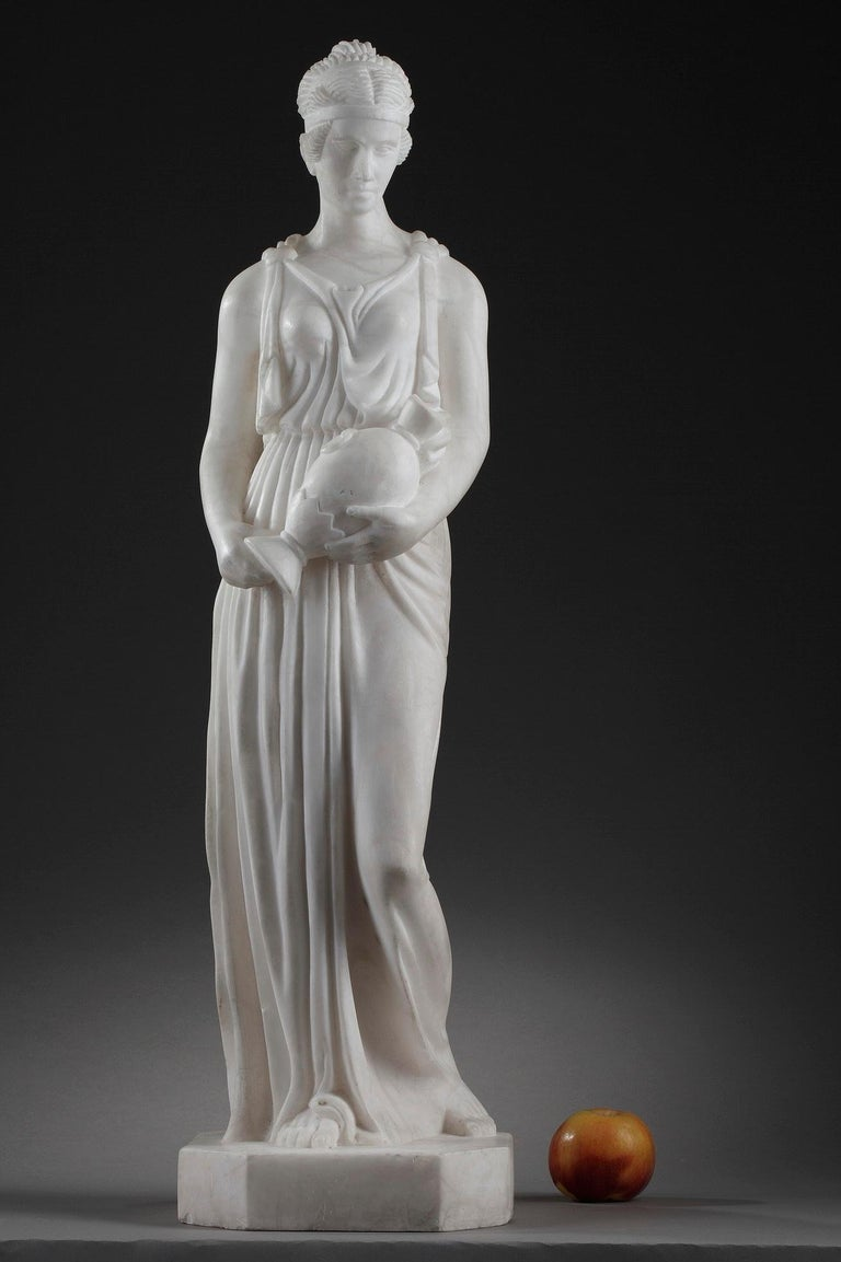 This Art Deco sculpture captures the Samaritan woman wearing a tunic draped about her body, carrying the jug. Her hair pulled up in a bun, is supported by a diadem. Carved from alabaster, the statue is a beautiful example of Classical style. The