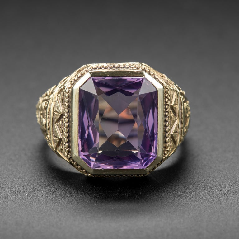 A bold and beautiful Egyptian Revival statement ring from the Art Deco era. Crafted by hand in 14k yellow gold, the ring showcases a beautiful rectangular-cut amethyst that measures approximately 14.40mm x 11.84mm and weighs about 8.79 carats. The