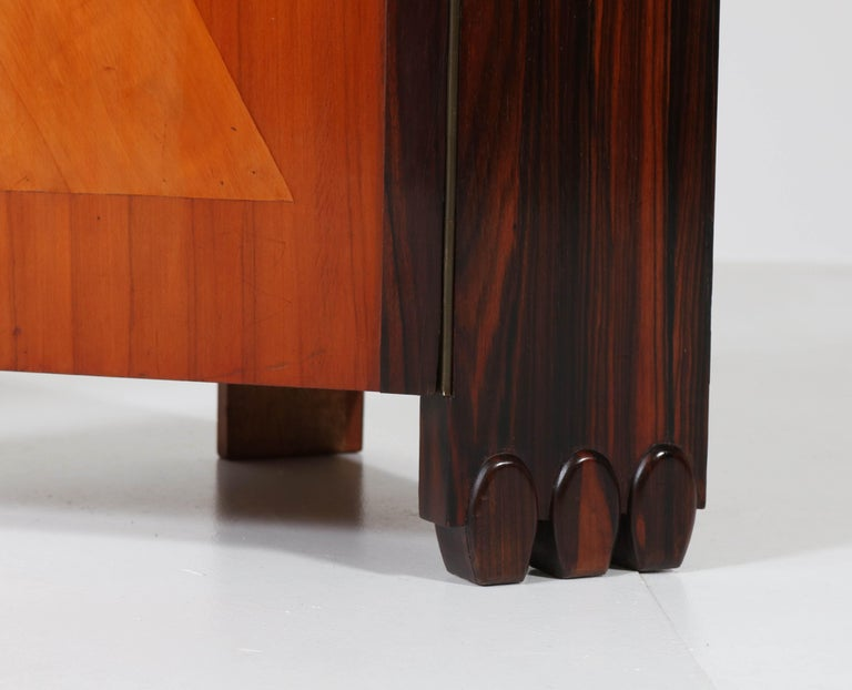 Wonderful and very rare pair of Art Deco Amsterdam School nightstands or bedside tables. Design by Max Coini, Amsterdam. Striking Dutch design from the 1920s. Sycamore, and Macassar with solid Macassar handles and glass tops. This pair is in