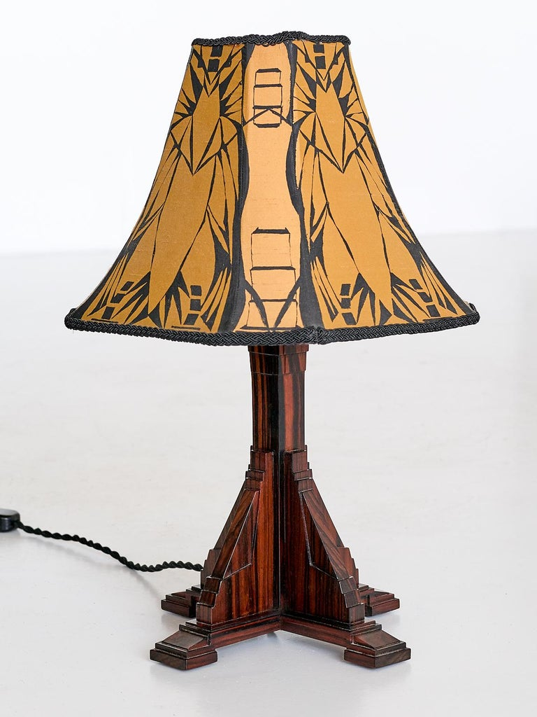 This elegant table lamp was produced in the Netherlands in the early 1930s. The tiered base rests on four square feet and is made of a veneered Macassar ebony with a striking wood grain. The meticulous manner in which the veneer has been applied