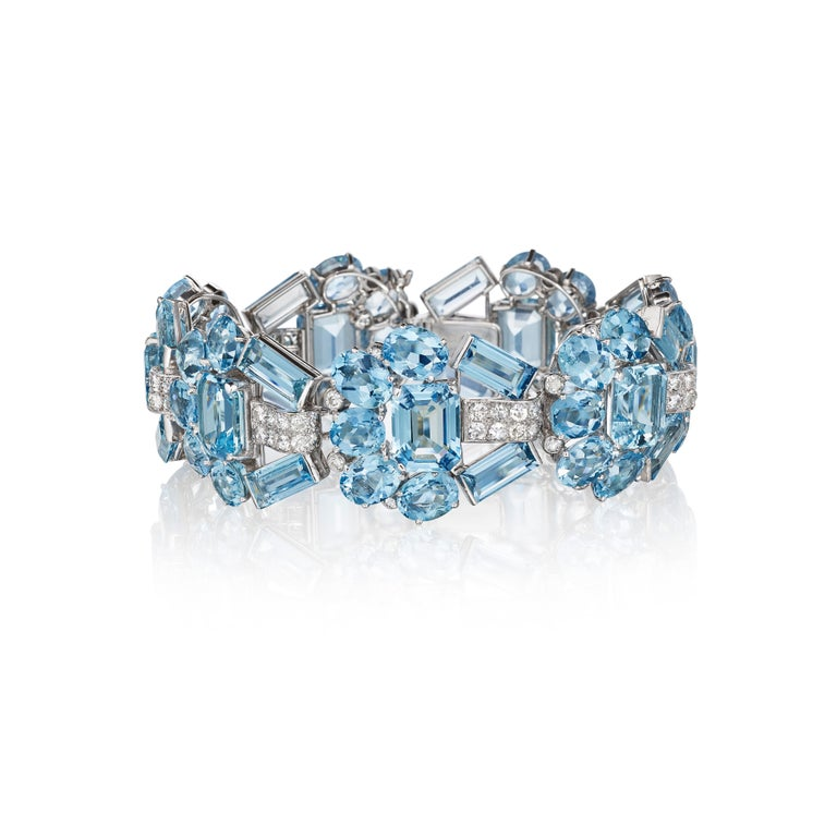 A demi-parure of a bracelet and ear clips, the bracelet composed of a series of oval, rectangular, and baguette-cut aquamarine segments joined by pave-set diamond-set links, the ear clips each composed as a swirl of oval aquamarines spaced with