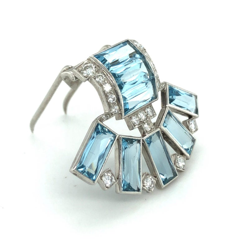 Superb Art Déco aquamarine diamond platinum clip by Cartier. Designed as an open fan and set with 8 baguette-shaped aquamarines totalling circa 9.60 carats and 20 old-cut and single-cut diamonds totalling circa 0.50 carats. The clip is completed by