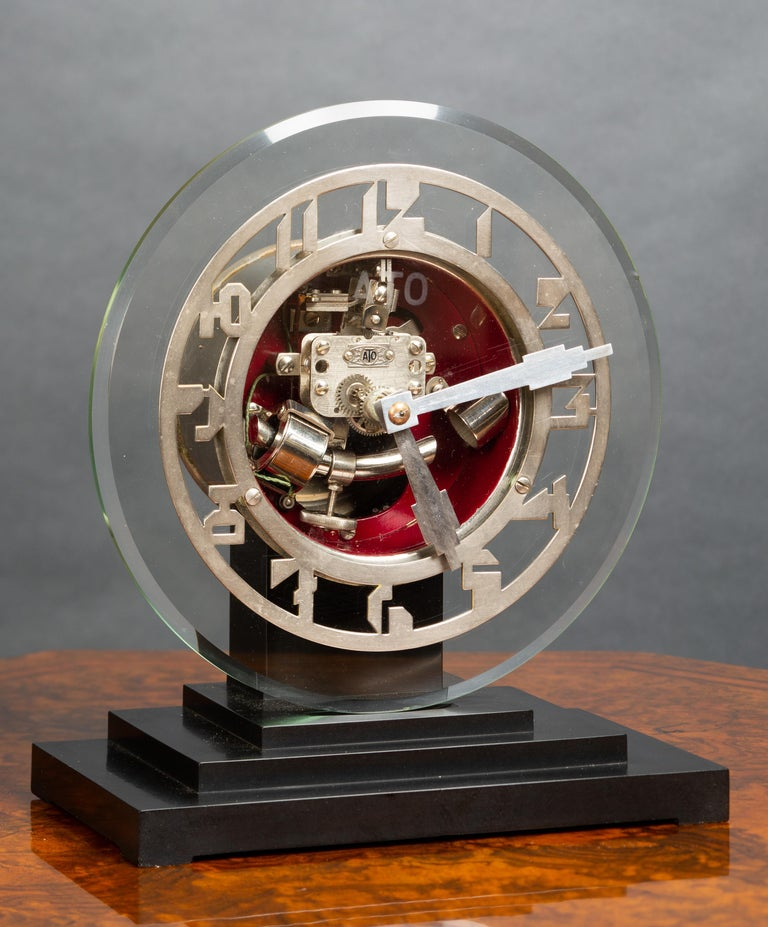 Art deco ATO clock standing on a three tiered Bakelite base supporting a glass dial with Art Deco style chrome numerals and chrome chapter ring.   The movement is powered by a 1.5 volt battery, the curved bar on the pendulum is a hollow rod