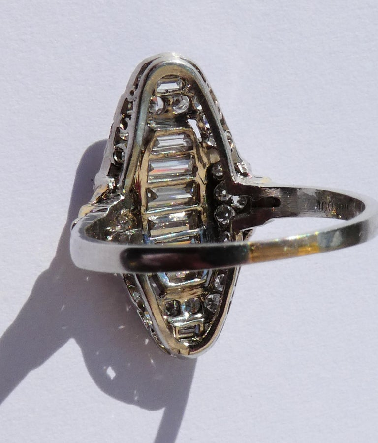 This ring was crafted circa 1920 in platinum in a beautiful geometrical design. In the center there are four diamonds in baguette cut and two diamonds in trapez cut in a domed setting which reminds us of a little bridge. These stones are in an