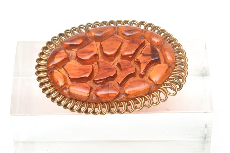 This fabulous carved art deco bakelite and brass trimmed oval pin brooch will make any outfit sing. The brass is overlapping loops as the exterior. This is not a common bakelite pin. The color of the bakelite has beautiful tones of orange amber