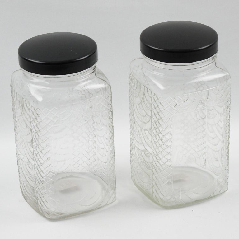 Lovely French Art Deco kitchen canister jar set of two pieces. Medium size container with a geometric shape. Molded glass with typical Art Deco design and a large area on one side for label display, topped with screw lid in shiny black Bakelite.