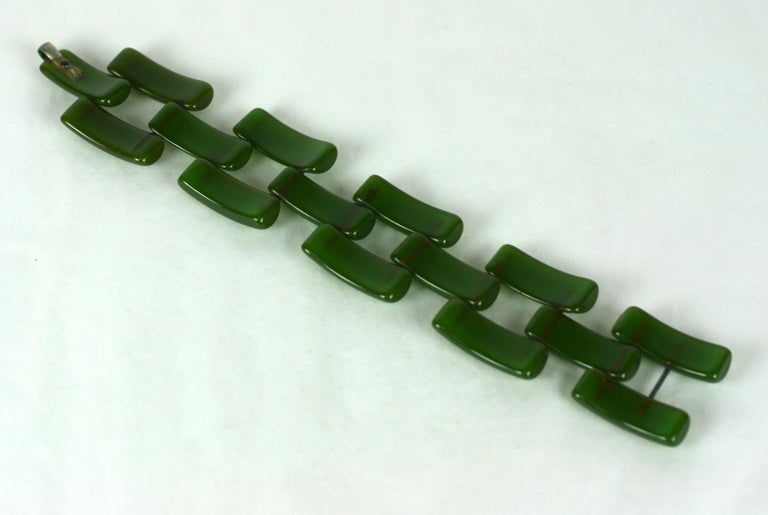 Art Deco Bakelite Link Bracelet in jade green. Curved strips of carved bakelite are pegged with metal rods to form a tank style flexible design. Wonderful translucent green coloration.  1930's USA. Self hook closure. Excellent condition. 8