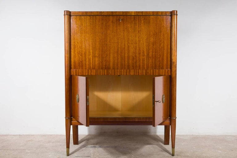 Art Deco bar cabinet manufactured by De Coene Frères in Belgium, circa 1940 walnut veneer with detailed brass lines and bronze stylized appliques designed with leaves and flowers, the wooden legs are finished with a brass top. Original good