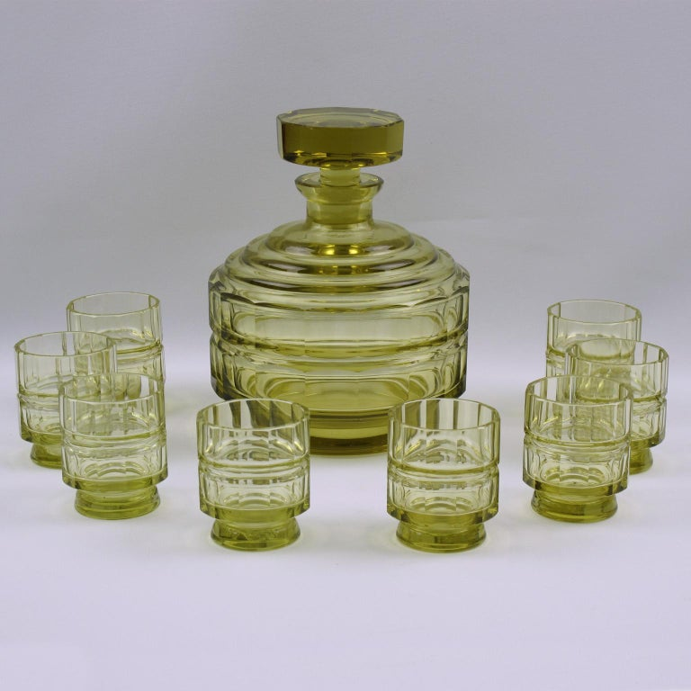 Lovely Art Deco crystal liquor or alcohol decanter set with eight matching cordial or aperitif glass. Very nice transparent olive oil color. The stopper, body, and glass are all cut and faceted to a fine standard. Heavy quality crystal with a great