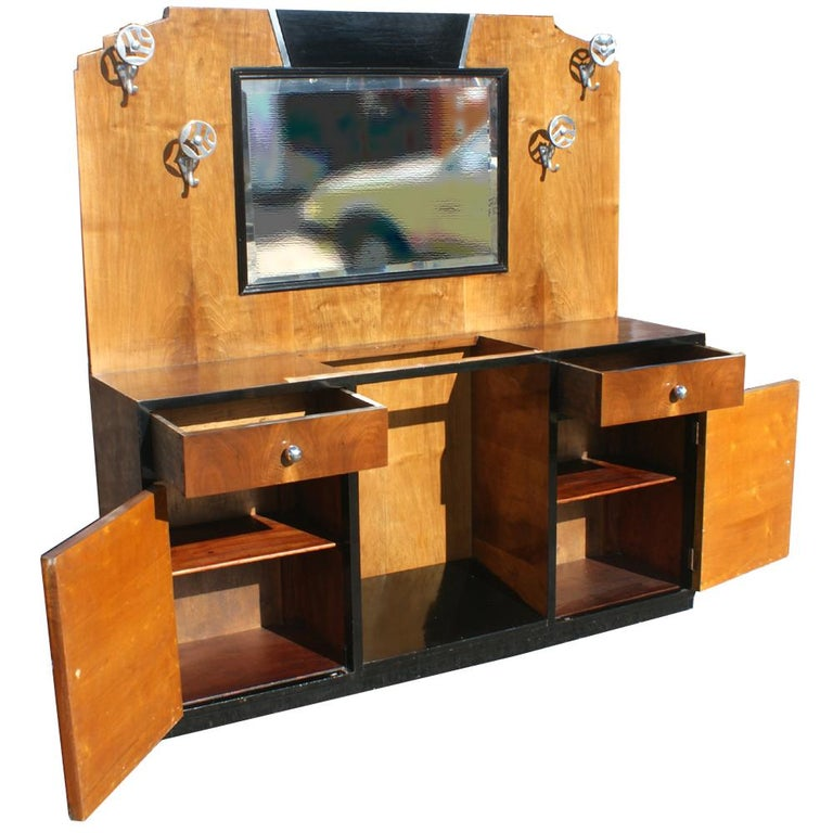 An Art Deco cabinet which could be used as a bathroom vanity.  Contrasting wood veneers and ebonized top and sides.  Shelved storage and drawers.  Beveled mirror.