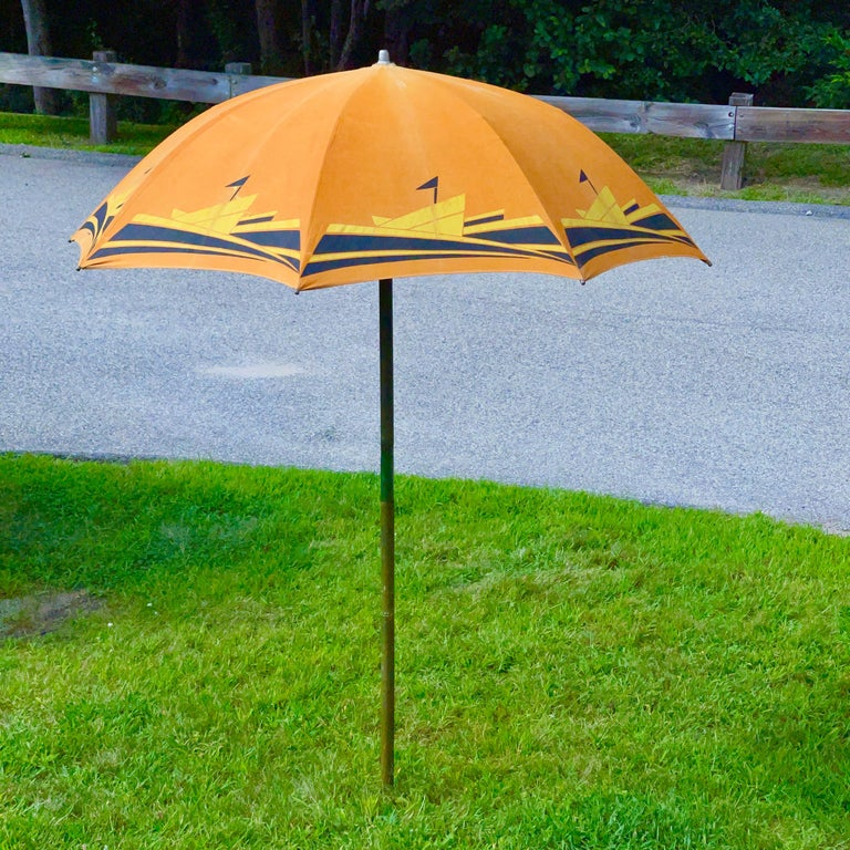 American Art Deco beach umbrella produced by the Troy Sunshade Co. circa 1936. Highly stylized streamlined silkscreened graphic yellow and black ocean liners steaming through the waves against a brilliant orange sky.  Cotton canvas duck on
