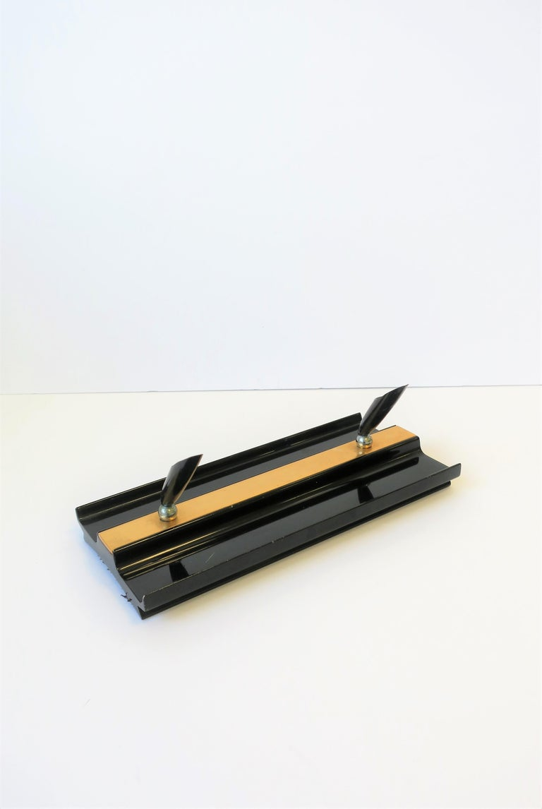 A beautiful and substantial modern Art Deco black and gold desk pen holder, with brass accent, circa 1970s.   Measurements include: 10 in. W x 4.75 in. D x 1 in. H.