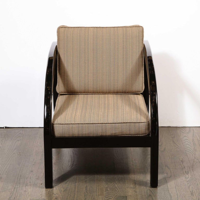 This elegant Art Deco chair was realized by the esteemed maker Modernage Co. in the United States, circa 1930. It features streamlined arms; a volumetric rectangular legs; and a geometric rectangular back with a support slat down the center- all in