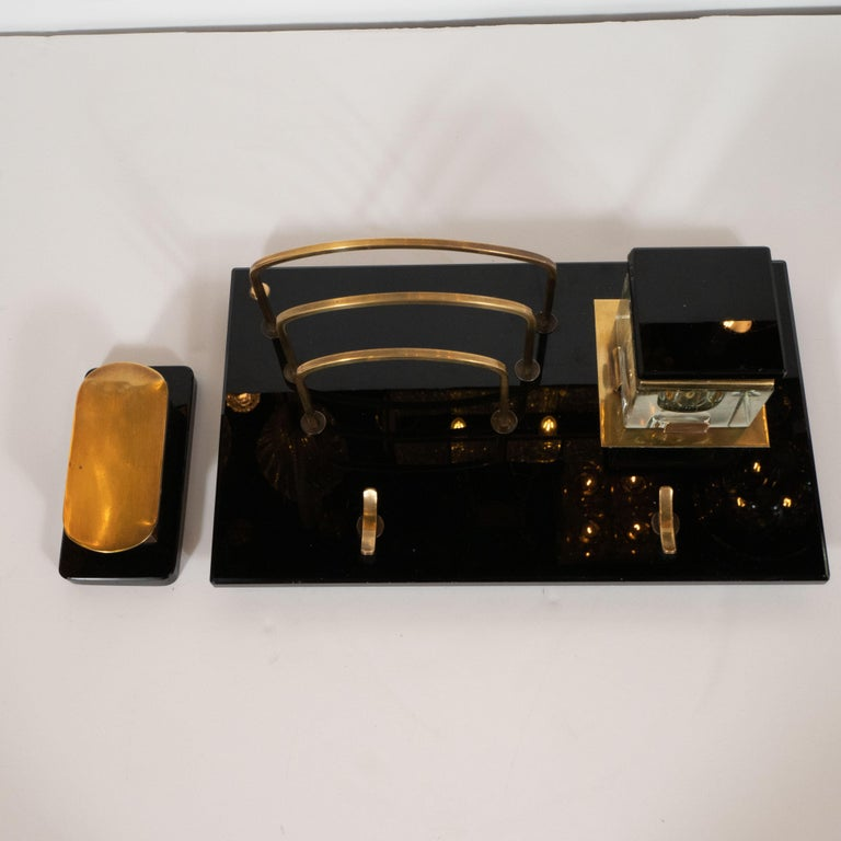 This American Art Deco desk set was produced, circa 1925. The set includes a pen rest, an inkwell, a letter holder and a stamp caddy. The letter holder, inkwell, and pen rest all sit on a lustrous black vitrolite plinth base with beveled edges. The