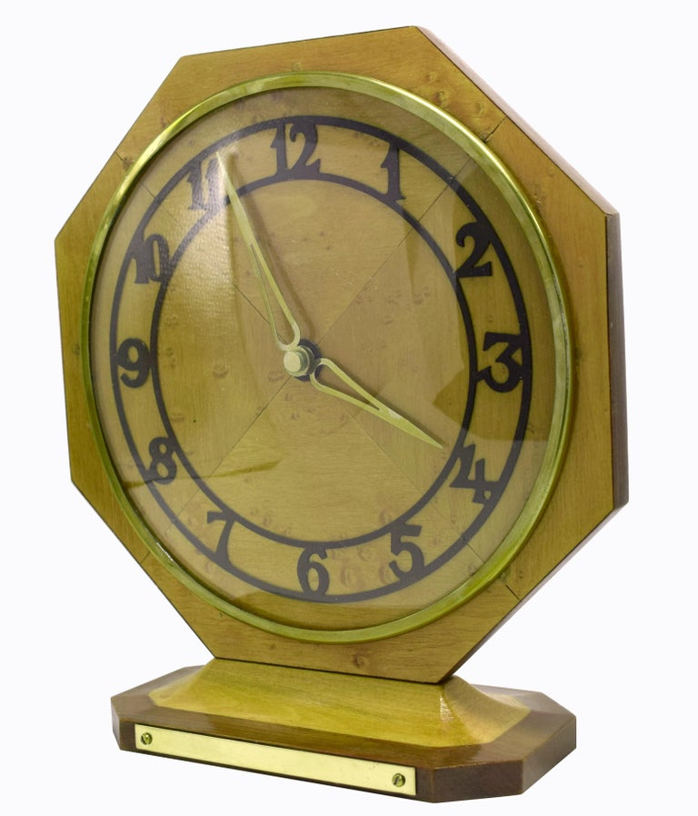 Very attractive 1930s Art Deco mantel (fireplace) clock in blonde Maple veneer. Hexagonal in shape supported on a triangular base, there is a plain plaque to the front of the plinth which could be inscribed if you so wish, ideal for gifting. A brass