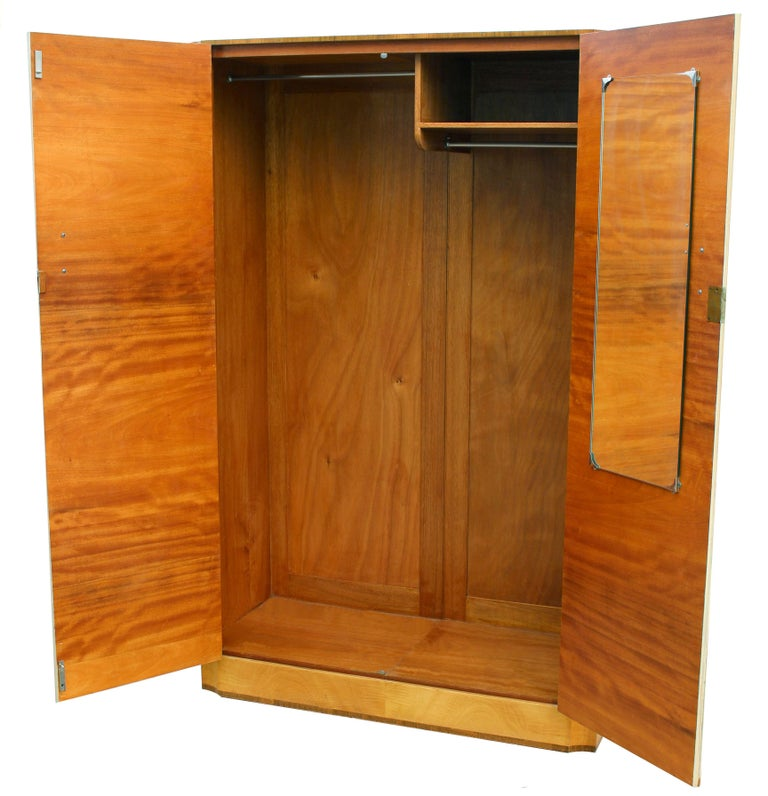 This beautiful wardrobe exudes quality and style. Book paged veneers in a true blonde tiger grain birch with contrasting straight grain walnut veneer banding to the top and base. Lovely detailing to the corners too which are inverted with a scallop